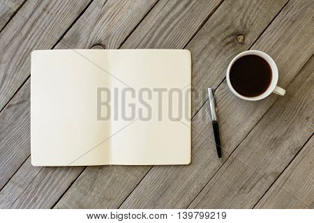 Open Notebook With Blank Pages Pen And Cup Of Coffee On Wooden Table. Top View