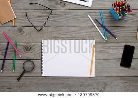 Notebook With Blank Pages Glasses Colored Pencils Snd Smartphone On Wooden Table In Home Office Top View