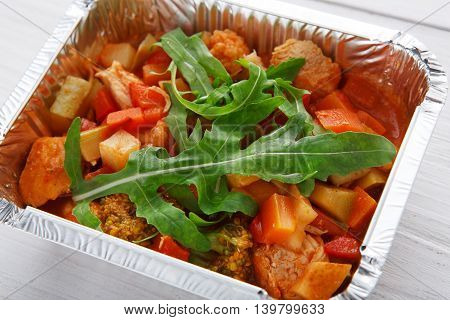 Healthy food and diet concept. Take away of fitness meal. Weight loss nutrition in foil box. Vegetable stew with soy meat, tomato sauce and arugula closeup at white wood