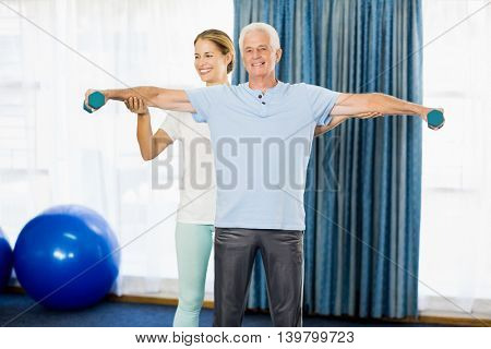 Instructor helping senior man with weights during sports class