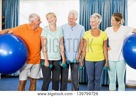 Seniors holding exercise ball and weights during sports class