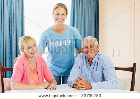 Volunteer taking care of senior couple at a retirement home