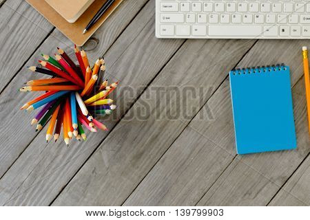 Colored Pencils On The Background Of The Desktop With Notebooks Pencils Pen And Keyboard Top View. Focus On Pencils