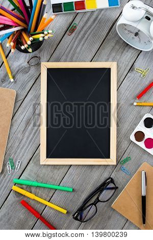 Small chalkboard in the frame school supplies on gray wooden table top view. Back to school concept
