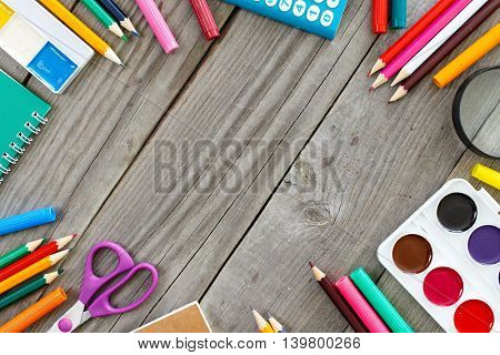 Frame with school different supplies on gray wooden desk. Top view