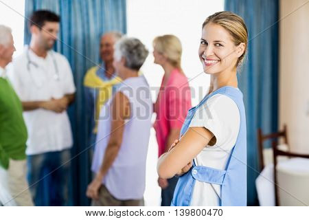 Nurse standing with arms crossed in a retirement home
