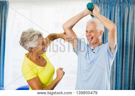 Senior woman feeling muscles of man in a sport studio