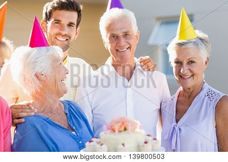 Nurse and seniors celebrating a birthday outside the retirement home