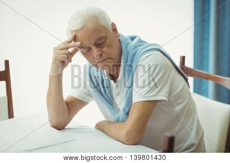 Sad senior man sitting at table in a retirement home