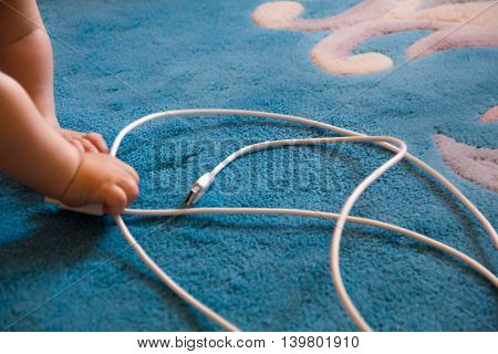 little cute baby playing with electrical wires the concept of child safety household appliances children at home