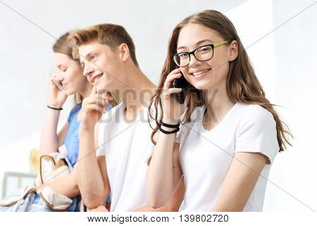 A group of teenagers with cell phone during a break classroom.