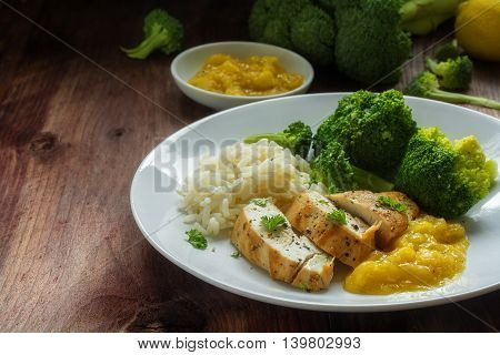 fried chicken breast fillet with stewed fruit sauce broccoli and rice on a dark rustic wooden table selected soft focus narrow depth of field
