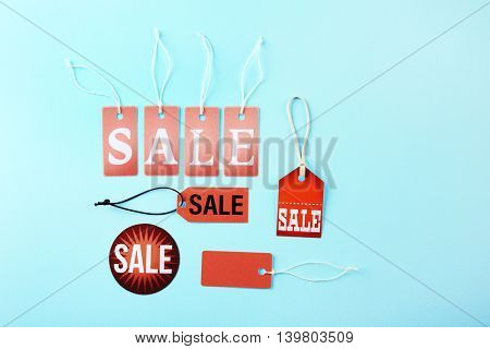 Paper tags with strings and word sale on blue background