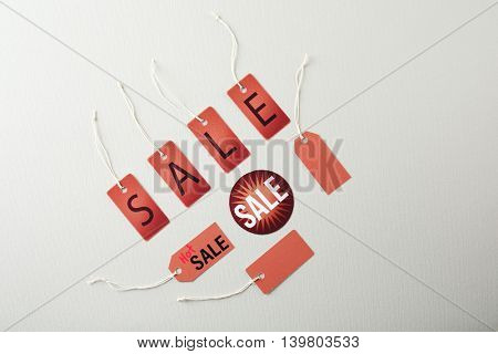 Paper tags with strings and word sale on grey background