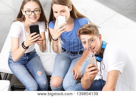 A group of teenagers with cell phones during a break classroom.