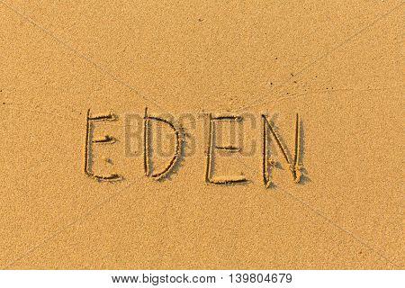 Eden - words hand-written on sand beach.