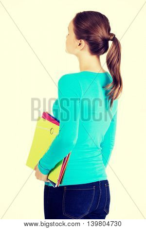 Attractive young woman holding files looking up.