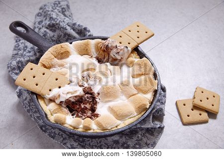 Smores dip baked in a cast iron pan with graham crackers