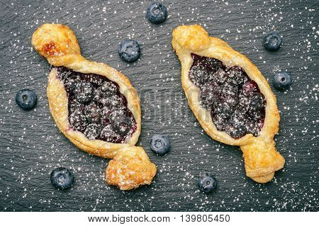 Puff pastries with blueberries on black background.