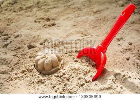 red toy shovel and molded sand in a sandbox or at the beach concept for family summer holiday at the seaside copy space selected focus narrow depth of field