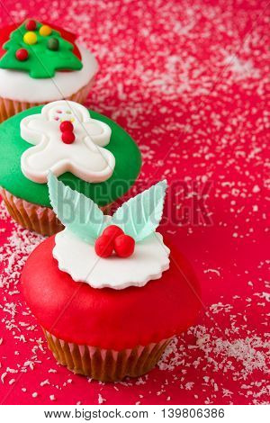 Some sweet christmas cupcakes on red background