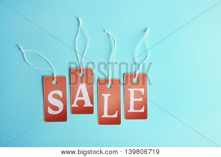 Brown paper tags with strings and word sale on blue background. Sale concept