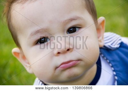funny and serious facial expression of the baby. A small child looking directly into the camera.