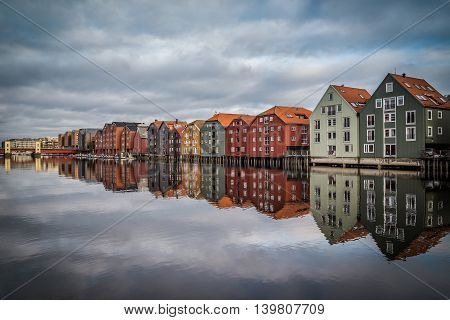 Old wooden houses in Trodheim Norway. Buildings build on wooden pillars at sea bay.