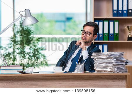 Young businessman in stress with lots of paperwork