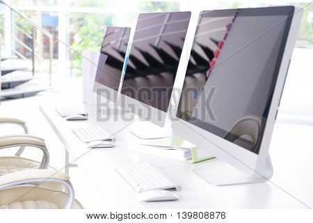 Modern computers on white wooden table in office