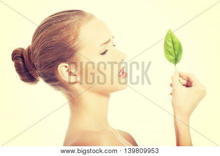 Beautiful caucasian woman eating fresh green leaf.
