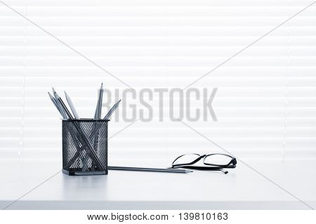 Office workplace with supplies on wood desk table in front of window with blinds. View with copy space. Toned
