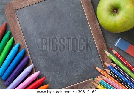 Chalk board for your text and colorful supplies. Back to school concept with copy space