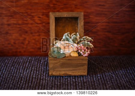 Wedding rings in a wooden box decorated with a rose