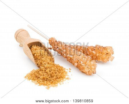 Brown sugar in a wooden scoop isolated on white background