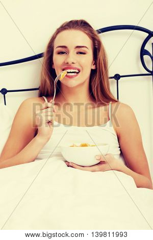 Beautiful caucasian woman eating fresh fruit in bed.