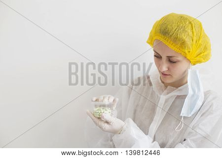 Scientist in white uniform with container full of pills