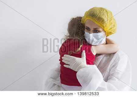 Woman in white protective suit soothes young girl