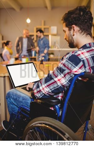 Graphic designer using laptop while colleagues interacting in background