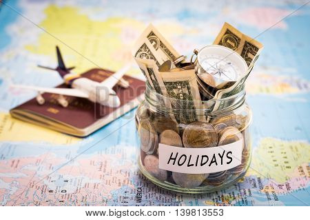 Holidays budget concept. Holidays money savings in a glass jar with compass passport and aircraft toy on world map