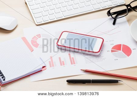 Office desk workplace with smart phone, charts and notepad on wooden table