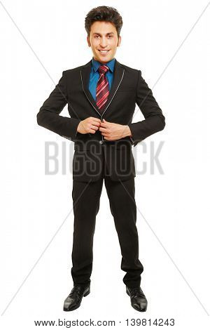 Smiling young businessman closing button of his jacket