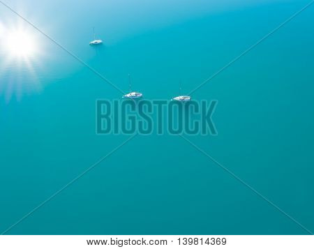 Beautiful aerial view of three yachts sailing on azure water