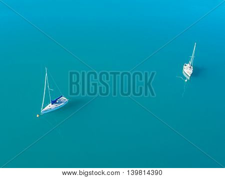 Beautiful aerial view of two yachts sailing on azure water