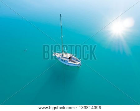 Beautiful aerial view of alone yacht sailing on azure water