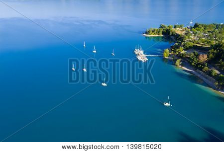 Beautiful aerial view of yachts sailing on azure water. Coastal shore on background