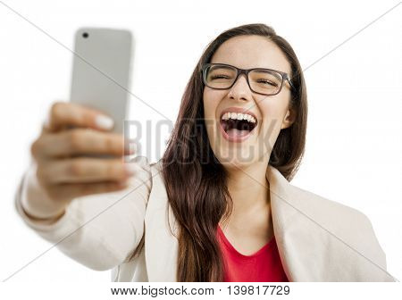 Beautiful woman making a  selfie with the phone, isolated over white background