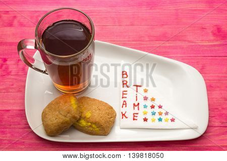 cup black tea and cookies with lemon cream on pink wood