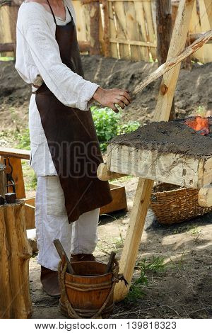 The male blacksmith in old clothes and apron is among the antiquities in the forge equipped for outdoor dining. With the help of special devices a person blows the fire.