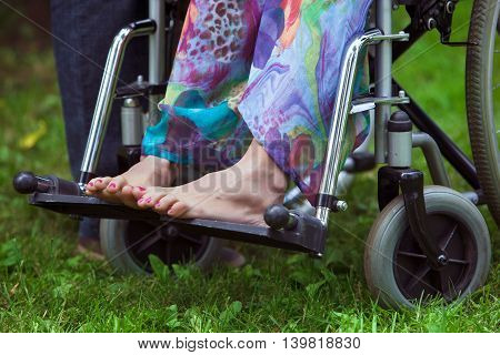 woman in a wheelchair in the Park. Feet closeup